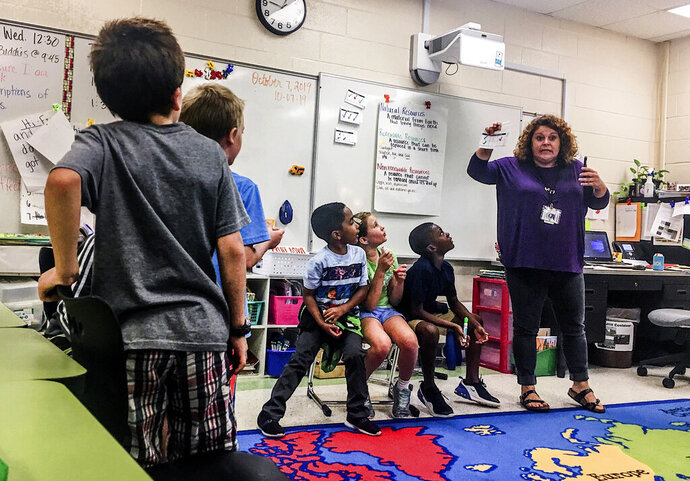 In this Oct. 7, 2019 photo, Dutch Fork Elementary students watch third grade teacher Kendall Donald as she explains how a growing human population puts pressure on the Earth's natural, renewable and nonrenewable resources in Irmo, S.C. Dutch Fork Elementary was named the first Green Ribbon school in South Carolina because of its focus on sustainability and environmental education. (Isabella Cueto/The State via AP)