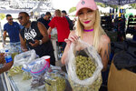 "FILE - In this Saturday, April 21, 2018 file photo a bud tender offers attendees the latest products of cannabis at the High Times 420 SoCal Cannabis Cup in San Bernardino, Calif. Businesses inside and outside the multibillion-dollar cannabis industry are using April 20, or ""420,"" to roll out marketing and social media messaging aimed at connecting with marijuana enthusiasts. (AP Photo/Richard Vogel, File)"