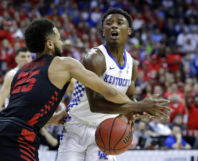 Kentucky's Ashton Hagans is fouled on his way to the basket by Houston's Galen Robinson Jr. (25) during the second half of a men's NCAA tournament college basketball Midwest Regional semifinal game Friday, March 29, 2019, in Kansas City, Mo. (AP Photo/Charlie Riedel)