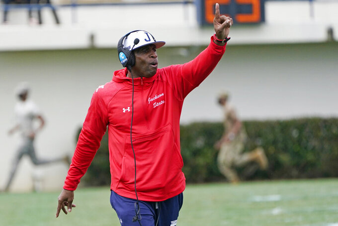 Jackson State football coach Deion Sanders calls out to his players during the first half of an NCAA college football against Edward Waters in Jackson, Miss., Sunday, Feb. 21, 2021. The game marks Sanders's collegiate head coaching debut. (AP Photo/Rogelio V. Solis)
