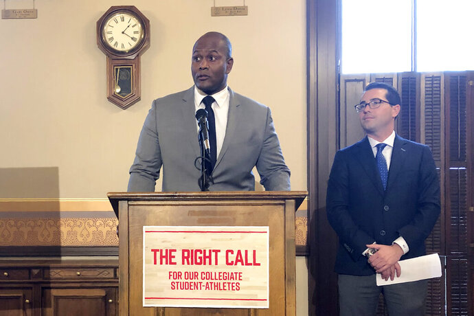 State Reps. Joe Tate, D-Detroit, left, and Brandt Iden, R-Ostemo, announce the introduction of bills that would let college athletes be compensated for the use of their name, image and likeness Wednesday, Nov. 6, 2019, at the Michigan Capitol in Lansing, Mich. The plan is modeled after a law that was recently enacted in California. (AP Photo/David Eggert)
