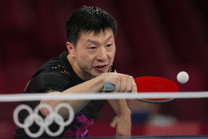 Ma Long of China, top, returns a shot during a gold medal match of the table tennis men's singles against Fan Zhendong of China at the 2020 Summer Olympics, Friday, July 30, 2021, in Tokyo. (AP Photo/Kin Cheung)