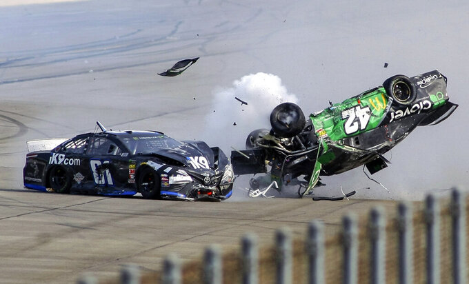FILE - In this April 28, 2019, file photo, Kyle Larson (42) flips as he makes contact with Jeffrey Earnhardt (81) on the back stretch during a NASCAR Cup Series auto race at Talladega Superspeedway in Talladega, Ala. The Associated Press looks at some of the events that would have been live the week of April 20-26: A big one at Talladega Superspeedway. Chase Elliott won last April ahead of a race-ending crash that flipped Kyle Larson a half-dozen times. Larson was fired last week by Chip Ganassi after using a racial slur during a live-streamed virtual race.  (AP Photo/Greg McWilliams, File)