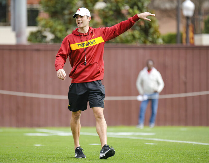 In this Tuesday, March 5, 2019 photo, provided by University of Southern California Athletics, new USC offensive coordinator Graham Harrell gestures during NCAA college football practice in Los Angeles. Harrell stepped into one of the highest-profile assistant jobs in college football after Kliff Kingsbury left USC without calling a play. The Trojans' new offensive coordinator is working hard to get up to speed in spring practice. (John McGillen/USC Athletics via AP)