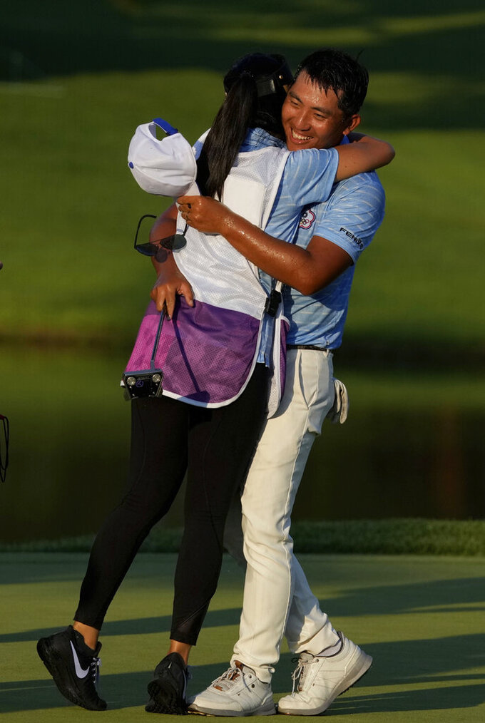 Cheng Pan of Taiwan is congratulated by his caddie after winning the bronze medal during the final round of the men's golf event at the 2020 Summer Olympics on Sunday, Aug. 1, 2021, in Kawagoe, Japan. (AP Photo/Andy Wong)