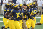 FILE - In this Sunday, Aug. 26, 2018, file photo, Michigan head coach Jim Harbaugh, center, walks the field as players jog around him during an open practice for the NCAA college football team at Michigan Stadium in Ann Arbor, Mich. Michigan plays Notre Dame on Saturday, Sept. 1, to open the college football season.  (AP Photo/Tony Ding, File)