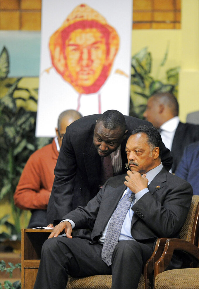 FILE - In this Thursday, April 26, 2012 file photo, Trayvon Martin family attorney Benjamin Crump, left, talks to Rev. Jesse Jackson during a rally in Los Angeles on behalf of the family of shooting victim Trayvon Martin. (AP Photo/Mark J. Terrill)
