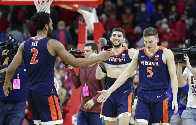 Virginia's Braxton Key (2), Kyle Guy (5) and Ty Jerome celebrate following the team's 66-65 overtime win over North Carolina State in an NCAA college basketball game in Raleigh, N.C., Tuesday, Jan. 29, 2019. (AP Photo/Gerry Broome)