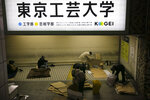 In this Wednesday, Jan. 15, 2020, photo, a group of homeless people are clustered at the Shinjuku Station near their belongings, in Tokyo. The dozens of homeless people sleeping rough in shuttered Tokyo subway stations worry that with Japan's image at stake authorities will force them to move ahead of the Olympics. (AP Photo/Jae C. Hong)