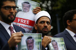 FILE - In this Monday, Oct. 8, 2018 file photo, members of the Turkish-Arab Journalist Association hold posters with photos of missing Saudi writer Jamal Khashoggi, as they hold a protest near the Saudi Arabia consulate in Istanbul. The disappearance of Khashoggi, during a visit to his country's consulate in Istanbul last week, raises a dark question for anyone who dares criticize governments or speak out against those in power: Will the world have their back? (AP Photo/Lefteris Pitarakis, File)
