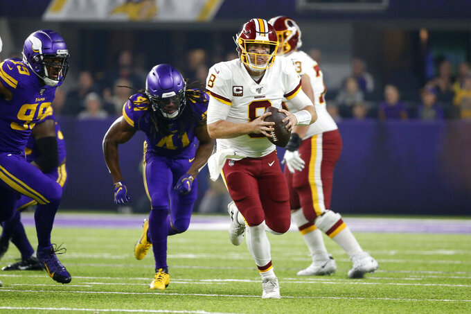 Washington Redskins quarterback Case Keenum (8) scrambles from Minnesota Vikings defensive back Anthony Harris (41) during the first half of an NFL football game, Thursday, Oct. 24, 2019, in Minneapolis. (AP Photo/Bruce Kluckhohn)
