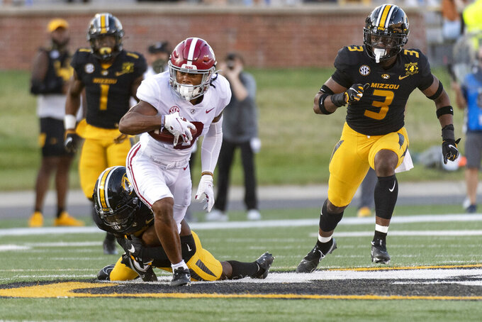 Alabama wide receiver John Metchie III, center, is tackled by Missouri's Jarvis Ware, left, during the first quarter of an NCAA college football game Saturday, Sept. 26, 2020, in Columbia, Mo. (AP Photo/L.G. Patterson)