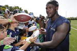 FILE - In this Aug. 6, 2018, file photo, Seattle Seahawks defensive end Frank Clark signs autographs following NFL football training camp, in Renton, Wash. The Kansas City Chiefs have agreed to acquire defensive end Frank Clark from the Seattle Seahawks in exchange for a first-round draft pick this year and a second-round pick in 2020. Almost immediately after word leaked of the trade on Tuesday, April 23, 2019, Clark and the Chiefs worked quickly to reach agreement on a five-year contract worth up to $105 million, according to a person with knowledge of the deal. The person spoke to The Associated Press on the condition of anonymity because the deal had not been announced by either team and was still pending a physical.(AP Photo/Ted S. Warren, File)