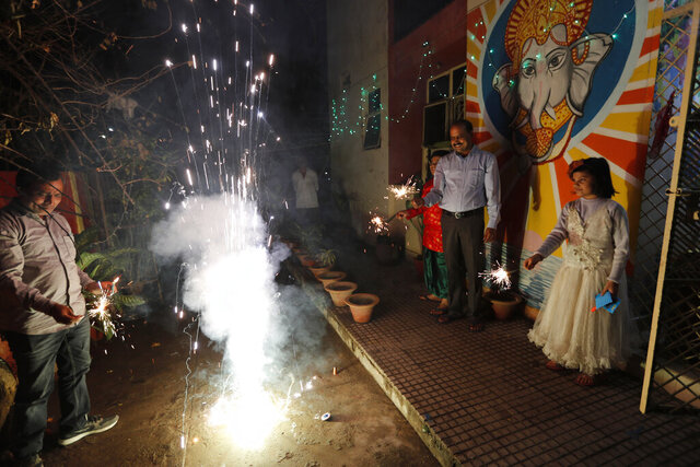 People play with fireworks during Diwali, the Hindu festival of lights, in Prayagraj, India, Saturday, Nov. 14, 2020. Hindus across the country are celebrating Diwali where people decorate their homes with lights and burst fireworks. (AP Photo/Rajesh Kumar Singh)