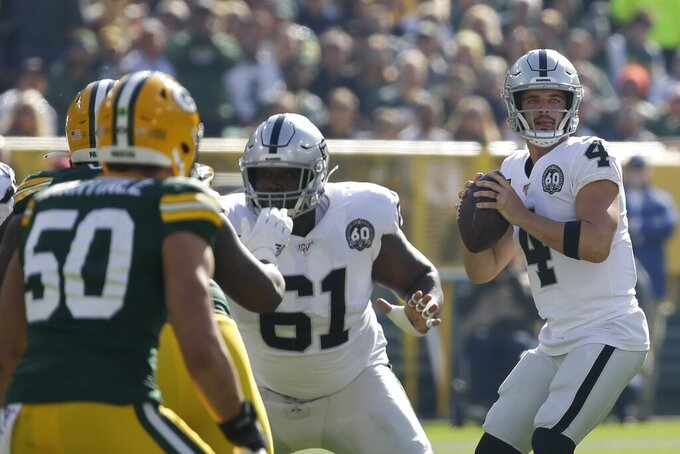 Oakland Raiders' Derek Carr drops back to pass during the first half of an NFL football game against the Green Bay Packers Sunday, Oct. 20, 2019, in Green Bay, Wis. (AP Photo/Mike Roemer)