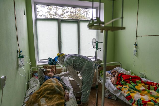 Dr. Oleh Hornostayev speaks to a coronavirus patient at a hospital intensive care unit in Stryi, Ukraine, on Tuesday, Sept. 29, 2020. Coronavirus infections in Ukraine began surging in late summer, and the ripples are hitting towns in the western part of the country. The government wants to avoid imposing a new lockdown, but officials acknowledge that the rising infections could make it necessary. (AP Photo/Evgeniy Maloletka)