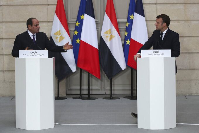 French President Emmanuel Macron, right, and Egyptian President Abdel-Fattah el-Sissi attend a joint press conference at the Elysee palace, Monday, Dec. 7, 2020 in Paris. Egyptian President Abdel-Fattah el-Sissi was meeting Monday with French President Emmanuel Macron for talks on fighting terrorism, the conflict in Libya and other regional issues as part of a state visit to France, amid criticism from human rights groups over the Egyptian leader's crackdown on dissent. (AP Photo/Michel Euler, Pool)