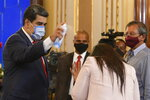 FILE - In this Dec. 8, 2020 file photo, Venezuela's President Nicolas Maduro playfully sprays a journalist with disinfectant as he exits a press conference at Miraflores Presidential Palace in Caracas, Venezuela, amid the new coronavirus pandemic. Attorneys for the cash-strapped government blame the impact of U.S. sanctions for its inability to make an initial $18 million down payment to the United Nations for doses of the U.N.-supplied vaccines, whose deadline has already passed. (AP Photo/Matias Delacroix, File)