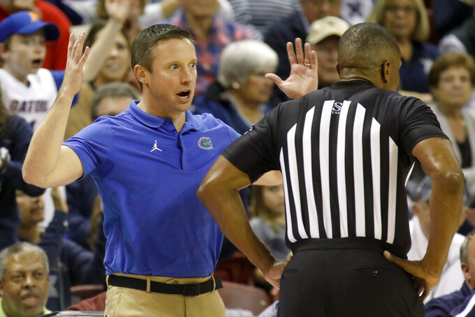 Florida's head coach Mike White can't believe a call while talking with official Ted Valentine during their game against Xavier in the first half of an NCAA college basketball game during the finals of the Charleston Classic Sunday, Nov. 24, 2019, in Charleston, SC. (AP Photo/Mic Smith)