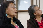In this Jan. 14, 2020, photo, Margaret Bitsue, left, and her sister Rita Bilagody, right, listen to presentations at a forum on missing indigenous men in Tuba City, Ariz. Bitsue's days are filled with prayer: that her son has a clear mind and that he remembers home, a traditional Navajo hogan at the end of a dirt road where a faded yellow ribbon hanging from a cedar tree points to her agony. Bitsue hasn't seen or heard from Brandon Sandoval, the youngest of her four children, in more than two years. (AP Photo/Felicia Fonseca)