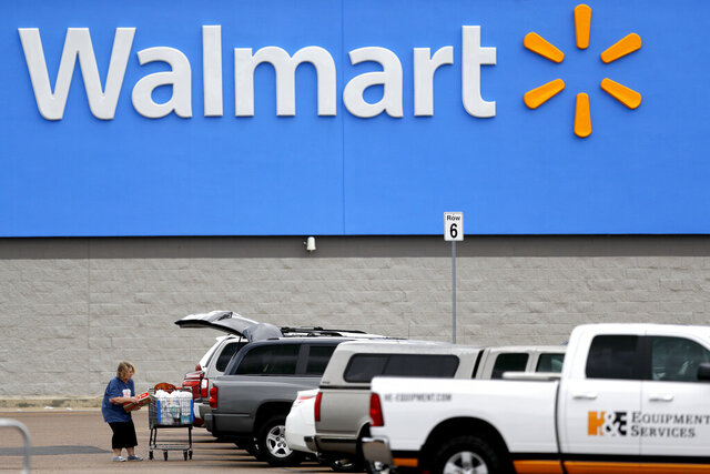 FILE - In this March 31, 2020 file photo, a woman pulls groceries from a cart to her vehicle outside of a Walmart store in Pearl, Miss. Walmart is teaming with the General Motors' Cruise autonomous vehicle unit to test automated package delivery in Arizona. (AP Photo/Julio Cortez, File)