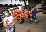 A worker pulls a handcart next to a member of the Red Cross, at the CEASA, Rio de Janeiro's main wholesale market, amid the new coronavirus pandemic in Rio de Janeiro, Brazil, Tuesday, June 23, 2020. (AP Photo/Silvia Izquierdo)