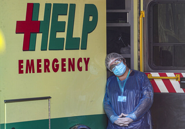 A medical worker wearing protective gear as a precaution against the spread of the new coronavirus, rests his head against an ambulance at the saturated emergency area of the San Jose hospital in Santiago, Chile, Tuesday, May 26, 2020. (AP Photo/Esteban Felix)