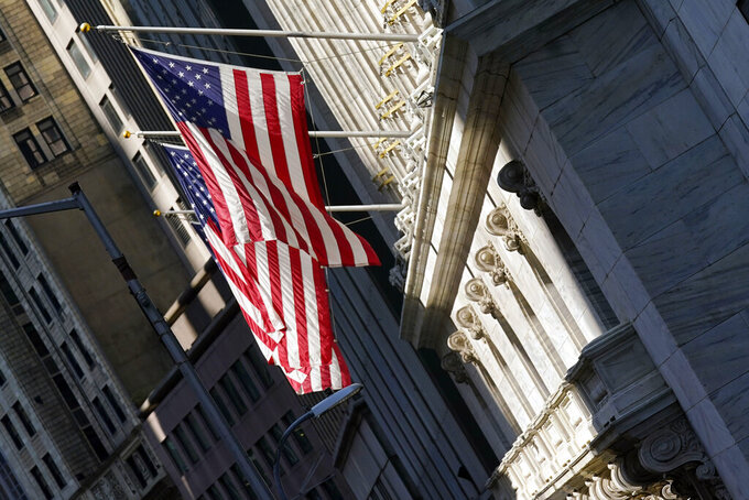 U.S. flags fly from the facade of the New York Stock Exchange, Monday, June 7, 2021. Stocks are opening mostly higher on Wall Street as gains for Big Tech companies offset weakness in banks and other parts of the market. The S&P 500 edged up 0.1% in the early going Wednesday, June 9.  (AP Photo/Richard Drew)