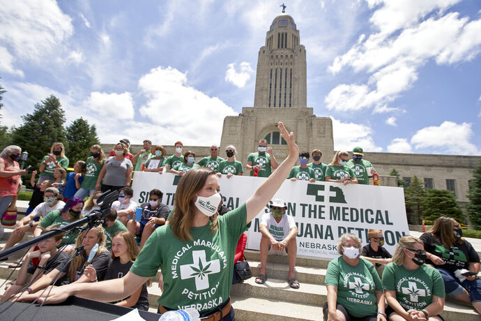 Neb. state Sen. Anna Wishart of Lincoln, center, who co-chaired the Nebraskans for Medical Marijuana campaign committee, speaks in front of the State Capitol in Lincoln, Neb., Thursday, July 2, 2020. Organizers of the Nebraskans for Medical Marijuana campaign said they've gathered 182,000 signatures from all 93 counties to allow the drug for medicinal use. To qualify for the ballot, the campaign needed to turn in more than 121,000 valid signatures, representing more than 10% of the voters in the state. Campaign officials also needed to collect signatures from at least 5% of voters in at least 38 Nebraska counties.(AP Photo/Nati Harnik)