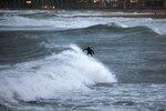 A man surfs the Mediterranean sea during strong winds in Barcelona, Spain, Sunday, Jan. 19, 2020. (AP Photo/Emilio Morenatti)
