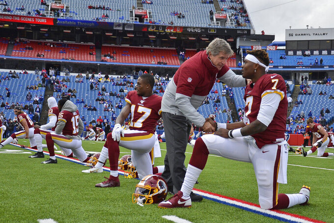 FILE - In this Nov. 3, 2019, file photo, Washington Redskins head coach Bill Callahan, left, talks with quarterback Dwayne Haskins before an NFL football game in Orchard Park, N.Y. The Redskins at the bye week of a lost season are a team without a definitive answer at quarterback, answers to questions on offense and defense and a visible organizational plan for the future. Callahan has repeatedly set the expectation at winning the next game and said he's receiving no direction from the front office on how to develop young players for the next few years. (AP Photo/Adrian Kraus, File)