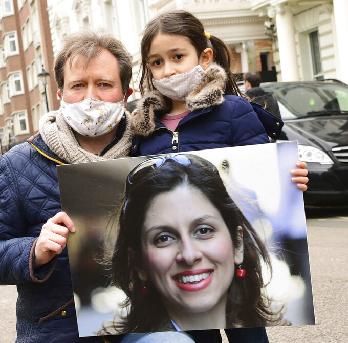 FILE - In this Monday March 8, 2021 file photo, Richard Ratcliffe sands with his daughter Gabriella as they hold a photo of his wife and her mother, Nazanin Zaghari-Ratcliffe, during a protest outside the Iranian Embassy in London. The supporters of a British-Iranian woman detained for five years in Iran says she has returned to court on fresh charges. The development casts uncertainty over her future following her release from prison last week. (Ian West/PA via AP, File)
