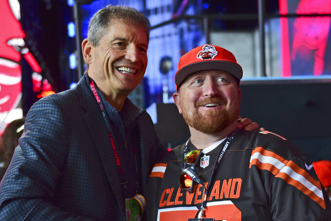 Former Cleveland Browns quarterback Bernie Kosar, left, poses for a photo with Tom Kline during the fourth round of the NFL football draft, Saturday, May 1, 2021, in Cleveland. (AP Photo/David Dermer)