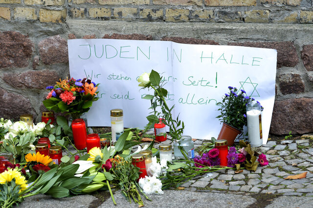 FILE -- In this Oct. 10, 2019 file photo, candles and flowers are placed in front of a synagogue in Halle, Germany after a heavily armed assailant ranting about Jews tried to force his way into the synagogue in Germany on Yom Kippur, Judaism's holiest day, then shot two people to death nearby in an attack.  Sign reads,