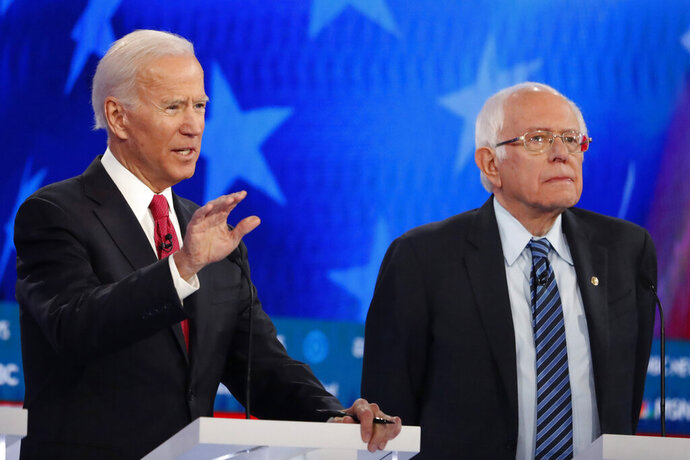 Democratic presidential candidate former Vice President Joe Biden, left, speaks as Democratic presidential candidate Sen. Bernie Sanders, I-Vt., listens during a Democratic presidential primary debate, Wednesday, Nov. 20, 2019, in Atlanta. (AP Photo/John Bazemore)