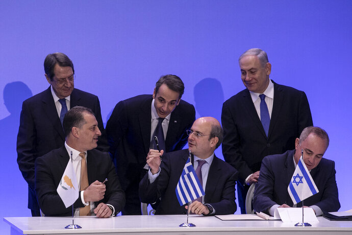 Cypriot Energy Minister Georgios Lakkotrypis, front left, Greek Energy Minister Kostis Hatzidakis, front center, and Israel's Minister of Energy and Water Yuval Steinitz sign an agreement as Greece's Prime Minister Kyriakos Mitsotakis, rear center, Cypriot President Nicos Anastasiadis, rear left, and Israeli Prime Minister Benjamin Netanyahu look on, in Athens, Thursday, Jan. 2, 2020. The leaders of Greece, Israel and Cyprus met in Athens Thursday to sign a deal aiming to build a key undersea pipeline, named EastMed, designed to carry gas from new rich offshore deposits in the southeastern Mediterranean to continental Europe. (AP Photo/Yorgos Karahalis)