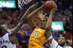 Tennessee guard Yves Pons (35) shoots while covered by Kansas guards Marcus Garrett, left, and Isaiah Moss, right, during the second half of an NCAA college basketball game in Lawrence, Kan., Saturday, Jan. 25, 2020. (AP Photo/Orlin Wagner)
