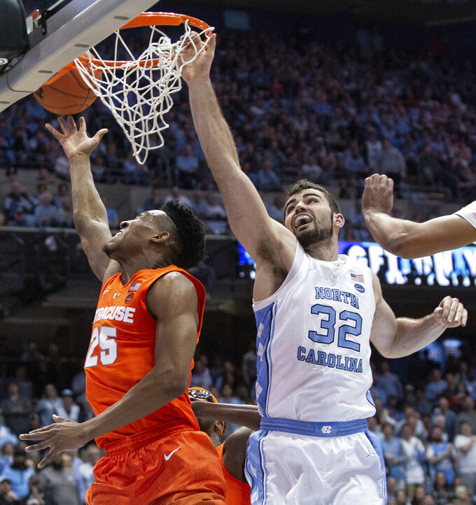 Syracuse's Tyus Battle (25) attempts a shot as North Carolina's Luke Maye (32) defends during the second half of an NCAA college basketball game in Chapel Hill, N.C., Tuesday, Feb. 26, 2019. (AP Photo/Ben McKeown)