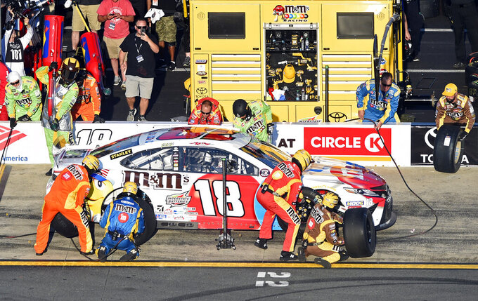 Crew members work on Kyle Busch's car during a NASCAR Cup Series auto race at Charlotte Motor Speedway in Concord, N.C., Sunday, May 26, 2019. (AP Photo/Mike McCarn)