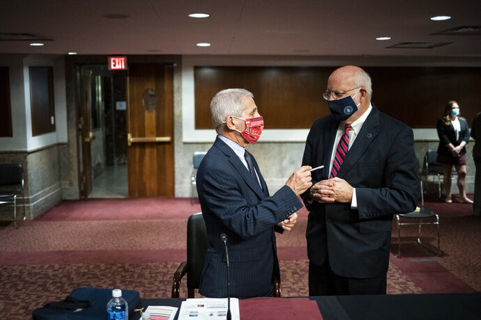 Director of the National Institute of Allergy and Infectious Diseases Dr. Anthony Fauci speaks with Dr. Robert Redfield, director of the Centers for Disease Control and Prevention during a Senate Health, Education, Labor and Pensions Committee hearing on Capitol Hill in Washington, Tuesday, June 30, 2020. (Al Drago/Pool via AP)