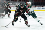 Arizona Coyotes right wing Christian Fischer (36) shields Minnesota Wild left wing Zach Parise from the puck during the second period during an NHL hockey game Friday, March 5, 2021, in Glendale, Ariz. (AP Photo/Rick Scuteri)