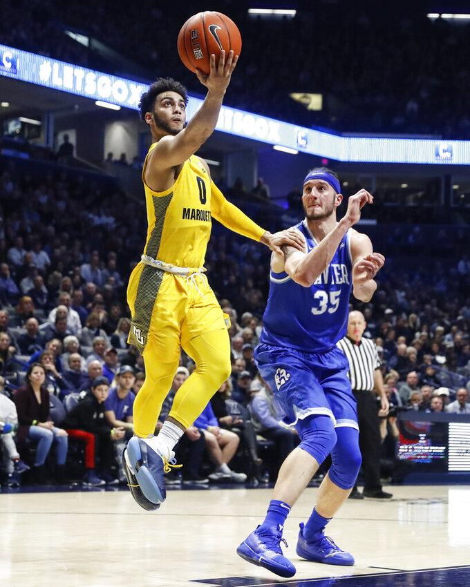 Marquette's Markus Howard (0) shoots against Xavier's Zach Hankins (35) in the second half of an NCAA college basketball game, Saturday, Jan. 26, 2019, in Cincinnati. (AP Photo/John Minchillo)