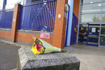 A floral tribute left outside Croydon Custody Centre where a police officer was shot in the early hours of Friday, Sept. 25, 2020, in Croydon, England. A British police officer has been shot dead inside a London police station while detaining a suspect. London's Metropolitan Police force said the officer was shot at the Croydon Custody Center in the south of the city early Friday.  (Aaron Chown/PA via AP)