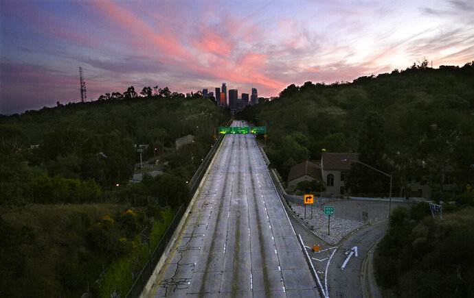 FILE - This April 26, 2020, file photo shows empty lanes of the 110 Arroyo Seco Parkway that leads to downtown Los Angeles during the coronavirus outbreak in Los Angeles, Calif. A record drop in U.S. energy consumption this spring was driven by less demand for coal that's burned for electricity and oil that's refined into gasoline and jet fuel. (AP Photo/Mark J. Terrill, File)