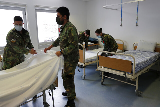 Soldiers prepare beds in consulting rooms being turned into a makeshift COVID-19 ward at the Military Hospital in Lisbon, Tuesday, Jan. 26, 2021. At the hospital, hundreds of troops have spent frantic weeks this month rushing to turn every available space into makeshift COVID-19 wards, as Portugal scrambles to cope with a sudden deluge of cases engulfing the public health system. (AP Photo/Armando Franca)