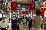 People walk inside historical Covered Bazar, one of homes of exchange offices in Istanbul, Friday, Aug. 7, 2020. Turkey's currency tumbled further Friday, hitting another record low. The Turkish lira dropped to 7.3677 against the dollar before making a recovery. The lira is down about 19% versus the U.S. currency since the beginning of the year. (AP Photo/Emrah Gurel)