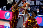 Arizona forward Ira Lee (11) drives between Southern California's Evan Mobley and Max Agbonkpolo (23) during the second half of an NCAA college basketball game, Thursday, Jan. 7, 2021, in Tucson, Ariz. (AP Photo/Rick Scuteri)