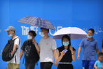 Visitors wear face masks to protect against COVID-19 as they walk at a tourist shopping street in Beijing, Tuesday, Aug. 3, 2021. Chinese authorities announced Tuesday mass coronavirus testing in Wuhan as an unusually wide series of COVID-19 outbreaks reached the city where the disease was first detected in late 2019. The current outbreaks, while still in the hundreds of cases in total, have spread much more widely than previous ones, reaching multiple provinces and cities including the capital, Beijing. (AP Photo/Mark Schiefelbein)