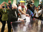 Leader of Poland's right-wing ruling party Jaroslaw Kaczynski, left, wearing a face mask for protection against the coronavirus, casts his ballot in the presidential election runoff in Warsaw, Poland, on Sunday, July 12, 2020, next to a man wearing a face mask of Kaczynski's likeness. The ruling Law and Justice party is backing the reelection bid of incumbent conservative President Andrzej Duda, against the liberal Warsaw Mayor Rafal Trzaskowski. Latest opinion polls suggested that the runoff will be decided by a very narrow margin. (AP Photo)