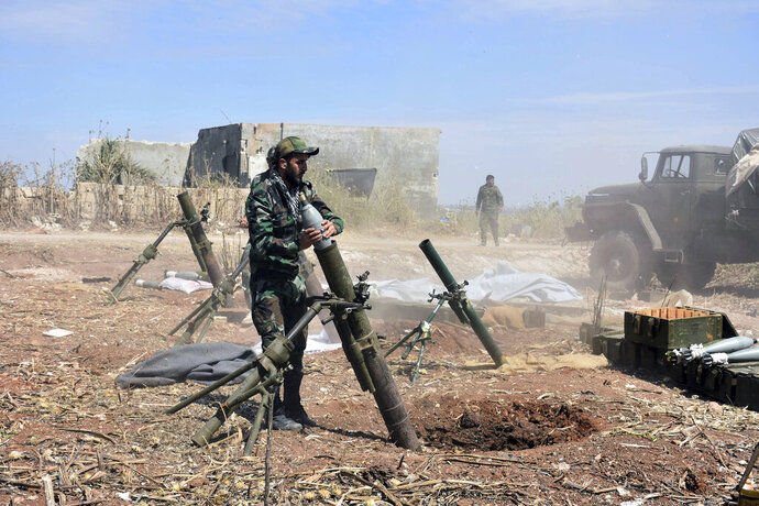 In this photo released by the Syrian official news agency SANA, Syrian army soldiers prepare to launch a mortar towards insurgents in the village of Kfar Nabuda, in the countryside of Hama province on Saturday, May 11, 2019. The Britain-based Syrian Observatory for Human Rights said government forces are now in control of nine villages forming an L shape at the far southern corner of the rebel stronghold. The villages include the strategic village of Kfar Nabuda and the elevated Qalaat Madiq, giving the government troops an advantage over the insurgents. (SANA via AP)